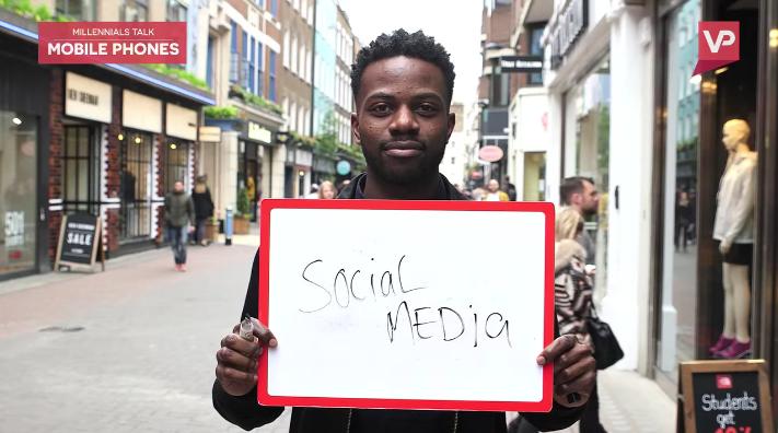Man holding a flip board reading social media.
